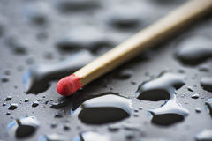 Dry match and raindrops on black metal surface Stock Photos