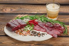 Dry meat with fresh herbs, chilli, condiments on a plate. beer is poured into a glass over wooden background. stock images