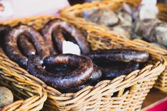 Dry meat salami or sausage on wicker basket stock images
