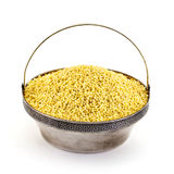 Dry millet in silver bowl isolated on white. Spilled millet. Royalty Free Stock Photos