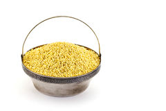 Dry millet in silver bowl isolated on white. Spilled millet. Stock Image