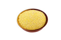 Dry millet in silver bowl isolated on white. Spilled millet. Stock Photos