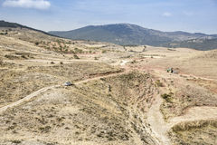 Dry mountain landscape on a summer day with a car and a tractor in Monforte de Moyuela, Teruel Royalty Free Stock Images