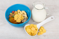 Dry muesli in blue bowl and jug milk on table Stock Image