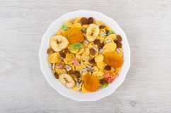 Dry muesli in white glass bowl on wooden table Stock Photos