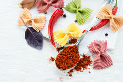 Dry multicolored farfalle pasta and smoked paprika Stock Photography