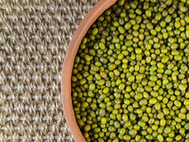 Dry mung bean in ceramic bowl. Dry mung bean in a ceramic pot on a background of sisal Royalty Free Stock Images