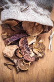 Dry mushrooms in jar on wooden table. Stock Photos