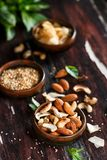 Dry Nuts. Almonds, Pecan, Coconut Flakes, Sesame Seeds. On wood background Stock Photography