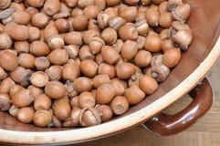 Dry oak acorns in ceramic bowl Stock Photo