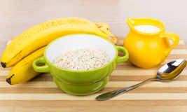 Dry oat flakes in green bowl, milk jug, bananas Stock Image