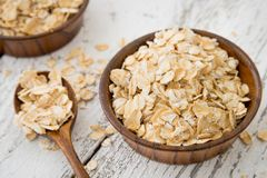 Dry oat flakes or oat grits cereals in craft wooden plate with s. Poon on white rustic wooden background close-up stock image