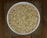 Dry oat flakes oatmeal in  bowl on wooden table, sacking. Tasty natural Royalty Free Stock Photos