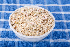 Dry Oatmeal in White Bowl on Blue Towel Royalty Free Stock Images