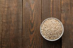 Dry oatmeal in a white bowl. food. healthy food. on a brown wooden table. with space for inscription. view from above stock photo