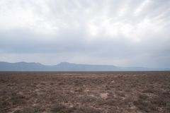 Dry and open field. With green shrubbery or plant life. Mountains in the horizon Royalty Free Stock Photos
