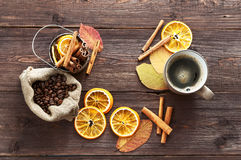 Dry orange and lemon, coffee beans in the bag, cinnamon. A Cup of hot coffee and fallen autumn leaves on wooden brown background Stock Images