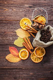 Dry orange and lemon, coffee beans in the bag, cinnamon and fallen autumn leaves. On wooden brown background Stock Image