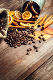 Dry orange and lemon, coffee beans in the bag, cinnamon and fallen autumn leaves on wooden brown background.  Royalty Free Stock Image