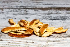 Dry orange peel. Just for use in an aromatic beverage on an old wooden white table Royalty Free Stock Images