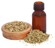 Dry oregano and essential oil. In an amber bottle Stock Photo