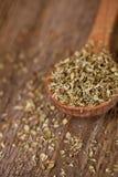 Dry oregano in wooden spoon Stock Photo