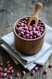 Purple grains-beens in a bowl. Dry organic purple grains-beens in a bowl on rustic wooden table. Haricot bean vegan protein source. Healthy food Royalty Free Stock Images