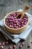 Purple grains-beens in a bowl. Dry organic purple grains-beens in a bowl on rustic wooden table. Haricot bean vegan protein source. Healthy food Stock Photos