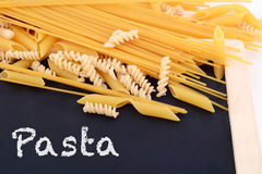 Dry pasta with blackboard. Royalty Free Stock Photos