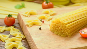 Dry pasta with cherry tomatoes and basil stock footage