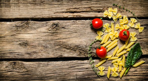 Dry pasta with cherry tomatoes and herb. Royalty Free Stock Image