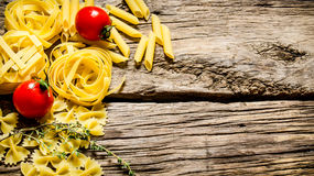 Dry pasta with cherry tomatoes and herb. Royalty Free Stock Photos
