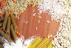 Dry pasta with lentil, flour and rice on wooden background. Whole wheat products on wood Stock Photos