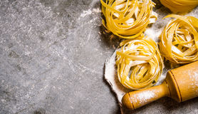 Dry pasta with a rolling pin and flour. Royalty Free Stock Photography