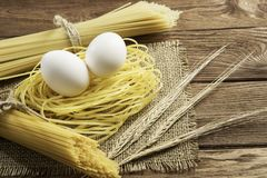Dry pasta on table. Close of spaghetti and eggs on table Stock Photos