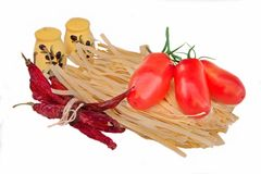 Dry Pasta Tagliatelle, chili pepper, fresh tomato and two shaker Royalty Free Stock Photos