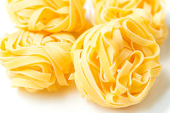 Dry pasta tagliatelle on tablecloth Stock Images