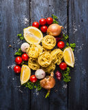 Dry pasta tagliatelle with tomatoes, herb and spices for tomato sauce, comosing Royalty Free Stock Image
