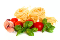 Dry pasta with tomatoes, basil and garlic. Selective focus Stock Photos