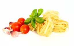Dry pasta with tomatoes, basil and garlic. Selective focus Royalty Free Stock Images