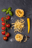 Dry pasta with tomatoes, basil and pepper Stock Photo