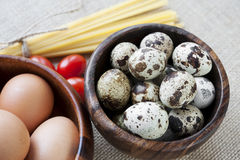 Dry pasta, tomatoes and eggs in wooden bowls on sa. Ck background. Closeup Royalty Free Stock Image