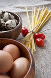 Dry pasta, tomatoes and eggs in wooden bowls on sa. Ck background. Closeup Stock Photo