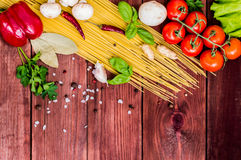 Dry pasta with tomatoes, herbs and spices for tomato sauce, on wooden background, top view Royalty Free Stock Photos
