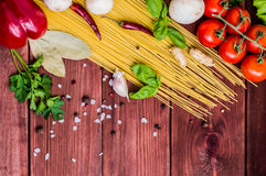 Dry pasta with tomatoes, herbs and spices for tomato sauce, on wooden background, top view Royalty Free Stock Photo