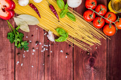 Dry pasta with tomatoes, herbs and spices for tomato sauce, on wooden background, top view Royalty Free Stock Images