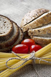 Dry pasta and tomatoes with sliced bread on sack background. Dry pasta and tomatoes, sliced bread with seeds on sack background. Closeup Royalty Free Stock Photography