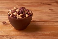 dry peanuts background. close up dry peanuts in clay bowl. Space for pext. Copyspace stock photos