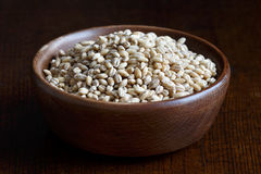 Dry pearl barley in brown wooden bowl. Royalty Free Stock Photos