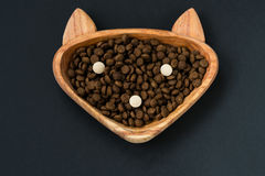 Dry pellet cat food and animal vitamins in wood bowl Royalty Free Stock Photos